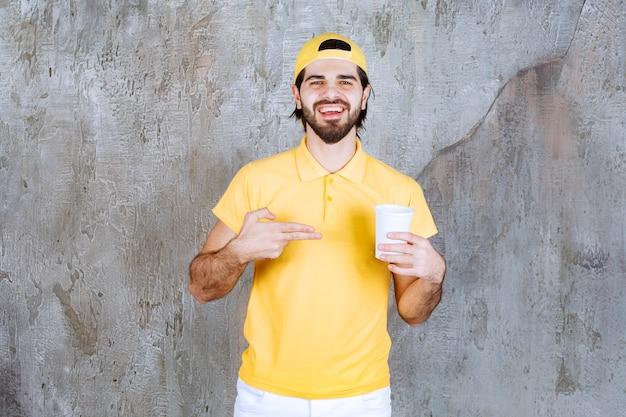 Kurier in gelber uniform mit einem einwegbecher.