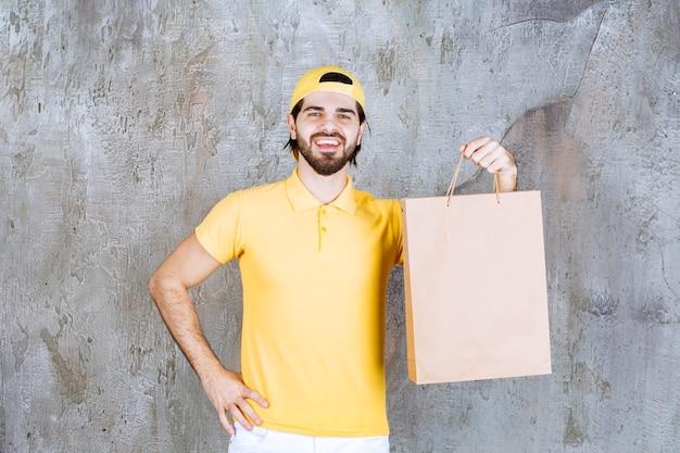 Kurier in gelber uniform mit einer einkaufstüte aus pappe