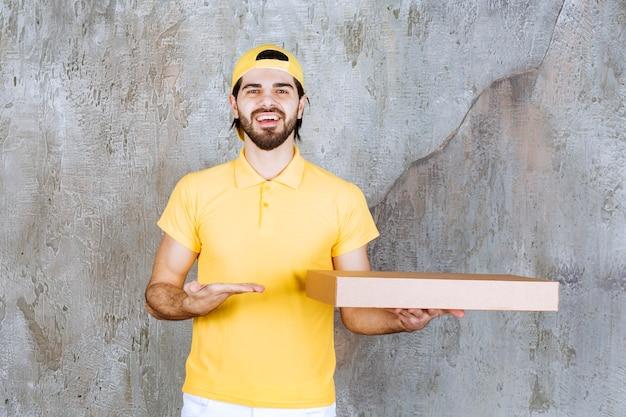 Kurier in gelber uniform mit einer pizzaschachtel zum mitnehmen
