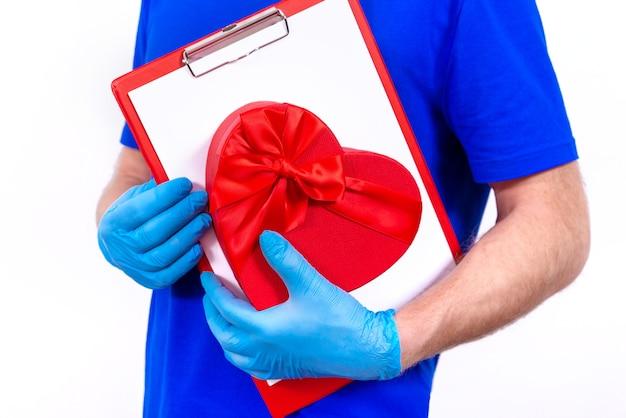 Kurier in schutzhandschuhen hält rote herzförmige geschenkbox zum valentinstag.