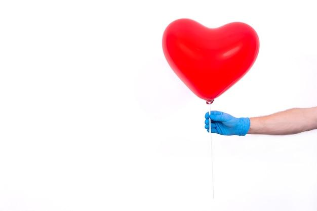 Kurier in schutzhandschuhen hält roten herzförmigen ballon zum valentinstag