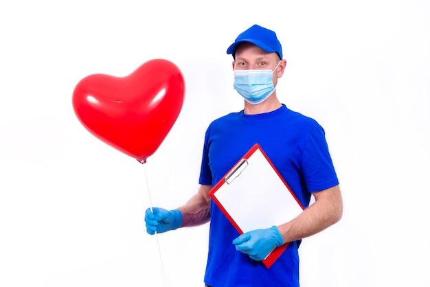 Kurier in schutzmaske, handschuhe hält rote herzförmige geschenkbox und ballon zum valentinstag