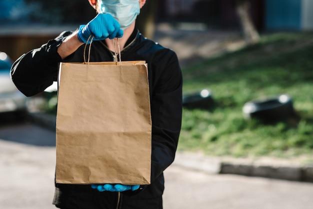Kurier in schutzmaske, medizinische handschuhe liefern essen zum mitnehmen. mitarbeiter halten kartonpaket. platz für text. lieferservice unter quarantäne, 2019-ncov, pandemisches coronavirus, covid-19.