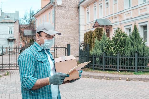 Kurier in schutzmaske und medizinischen handschuhen liefert essen zum mitnehmen. sonniger tag.