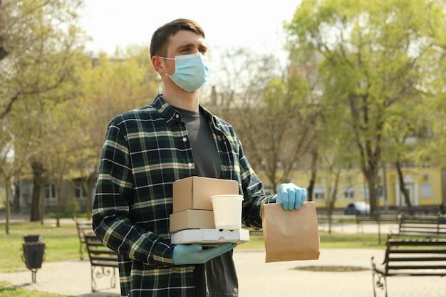 Kurier in schutzmaske und medizinischen handschuhen liefert essen zum mitnehmen