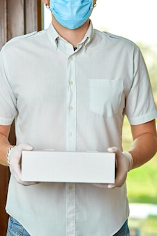 Kurier, lieferbote in medizinischen latexhandschuhen und maske liefert sicher online-einkäufe während des coronavirus