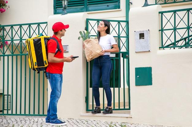 Kurier liefert papierpaket mit lebensmitteln an kunden. frau, die liefermann mit tablette und lebensmittel vom lebensmittelgeschäft trifft. versand- oder lieferservicekonzept