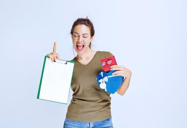 Kurier lieferte rote und blaue geschenkboxen und bat um unterschrift auf der checkliste