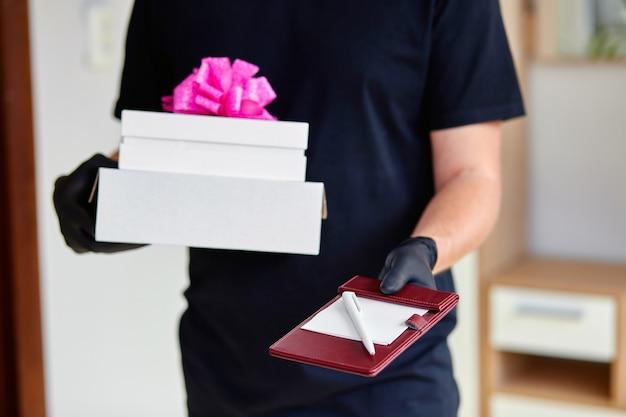 Kurier mann in schwarz mit schutz medizinische maske und handschuhe kontaktlose lieferung präsentiert, geschenkbox während einer coronavirus-epidemie