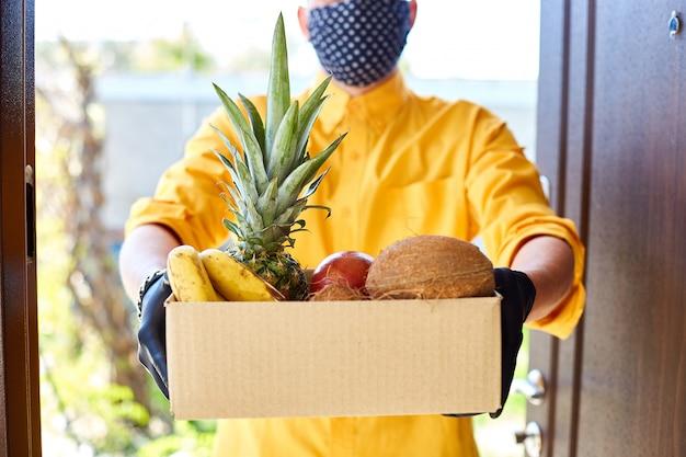 Kurier mann lieferbox mit exotischen früchten essen, kontaktlose lieferung.
