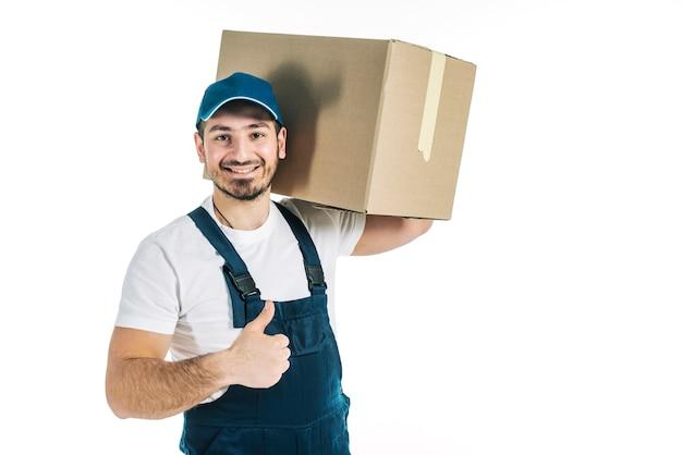 Kurier mit dem paket, das daumen-oben gestikuliert