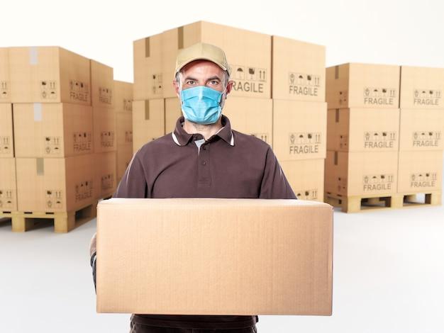 Kurier mit maske und paket in der hand, palette von kartons.