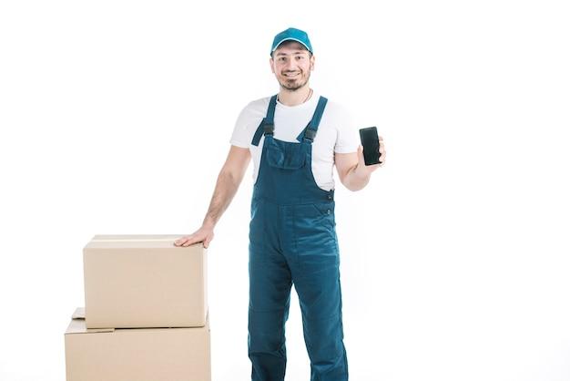 Kurier mit smartphone in der nähe von paketen