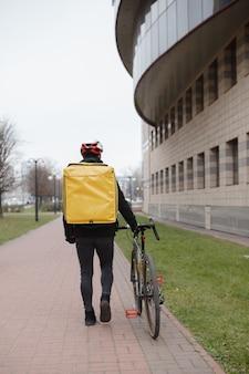Kurier mit thermo-lieferrucksack, der mit seinem fahrrad durch die stadt geht