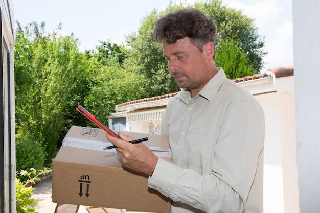Kurier standing at front door mit digital-tablet