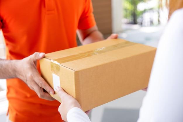 Kurierdienst-lieferungsmann, der dem kunden paketkasten gibt