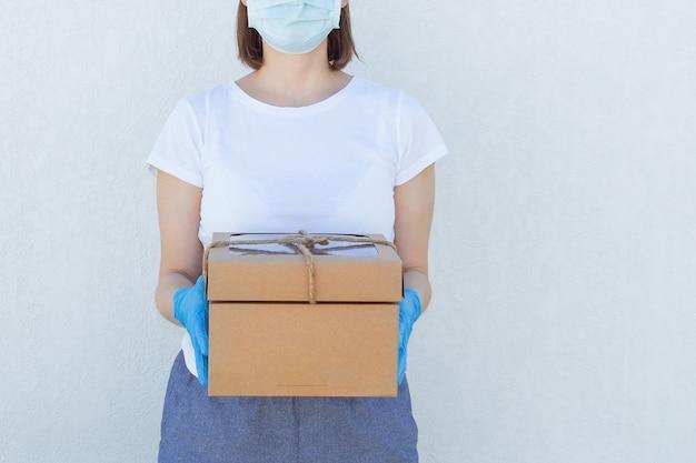 Kurierfrauen in medizinischer maske und handschuhen, die pappkartons halten.