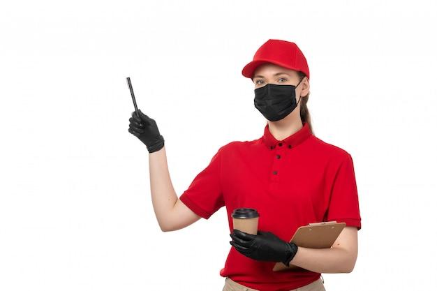 Kurierin der vorderansicht in den roten handschuhen der roten kappe der roten kappe und der schwarzen maske zusammen mit braunen jeans, die kaffee auf weiß halten
