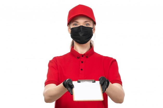 Kurierin der vorderansicht in den roten handschuhen des roten hemdes der roten kappe und der schwarzen maske, die notizblock auf weiß hält