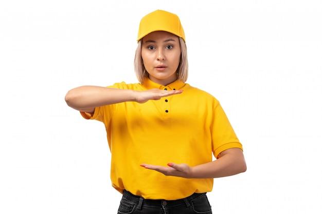Kurierin der vorderansicht in der gelben kappe des gelben hemdes und in den schwarzen jeans, die größe mit ihren händen auf weiß zeigen