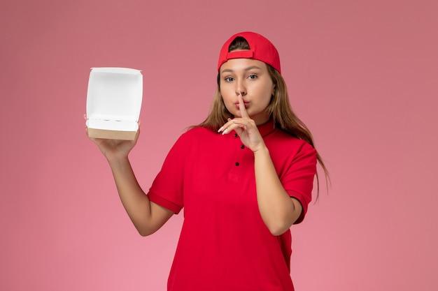 Kurierin der vorderansicht weiblicher kurier in roter uniform und umhang, die leeres liefernahrungsmittelpaket hält, das bittet, auf hellrosa wand ruhig zu sein, einheitliches lieferserviceunternehmen