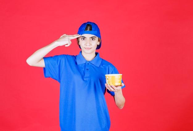 Kurierin in blauer uniform, die einen gelben nudelbecher hält und eine gute idee hat. Kostenlose Fotos