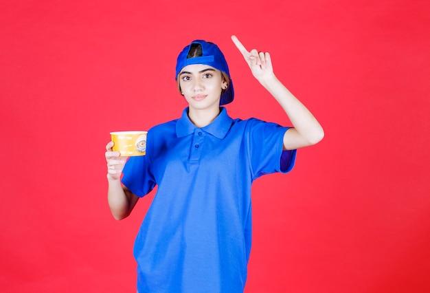 Kurierin in blauer uniform, die einen gelben nudelbecher hält und eine gute idee hat.