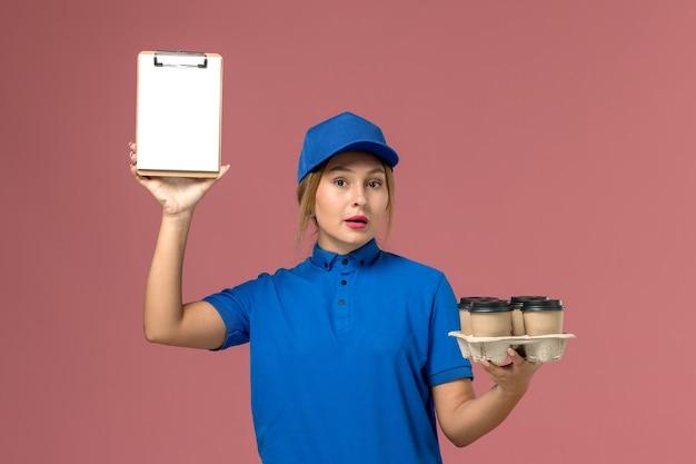 Kurierin in blauer uniform, die notizblock zusammen mit braunen lieferbechern kaffee auf hellrosa, arbeitsdienstuniformlieferung hält