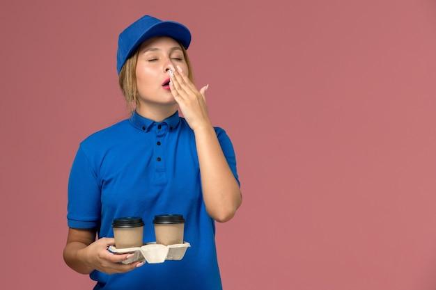 Kurierin in blauer uniform mit tassen kaffee, die auf rosa, dienstuniform-lieferauftrag gähnen