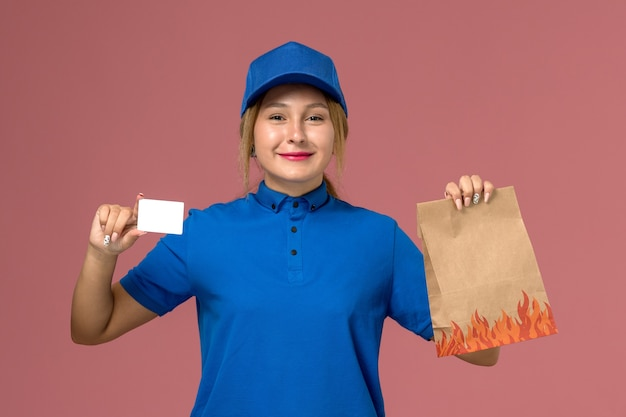 Kurierin in blauer uniform mit weißer karte und lebensmittelpaket auf hellrosa, dienstuniform-lieferauftrag