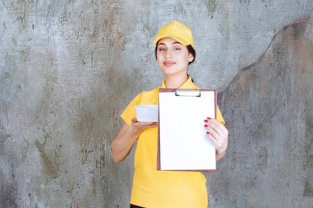 Kurierin in gelber uniform, die eine tasse zum mitnehmen hält und die aufgabenliste zur unterschrift vorlegt