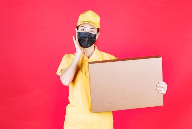 Kurierin in gelber uniform und schwarzer maske, die den karton hält, sieht verwirrt und nachdenklich aus