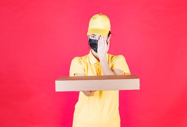 Kurierin in gelber uniform und schwarzer maske, die den karton hält und ein auge schließt