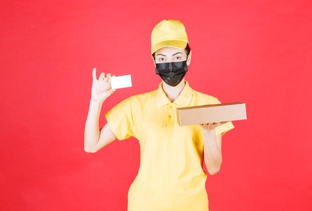 Kurierin in gelber uniform und schwarzer maske, die den karton hält und ihre visitenkarte vorlegt