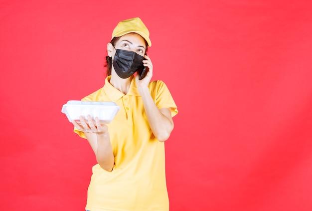 Kurierin in gelber uniform und schwarzer maske, die ein paket zum mitnehmen hält und bestellungen per smartphone entgegennimmt, während sie mit dem telefon spricht
