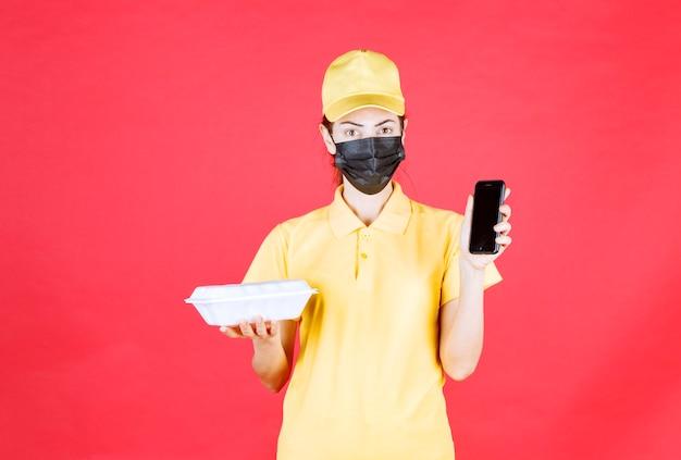 Kurierin in gelber uniform und schwarzer maske, die ein paket zum mitnehmen hält und bestellungen per smartphone entgegennimmt