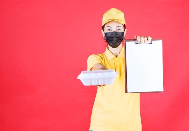 Kurierin in gelber uniform und schwarzer maske, die ein paket zum mitnehmen hält und die unterschriftenliste vorlegt