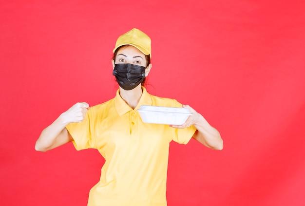 Kurierin in gelber uniform und schwarzer maske, die ein paket zum mitnehmen hält und ihre faust zeigt