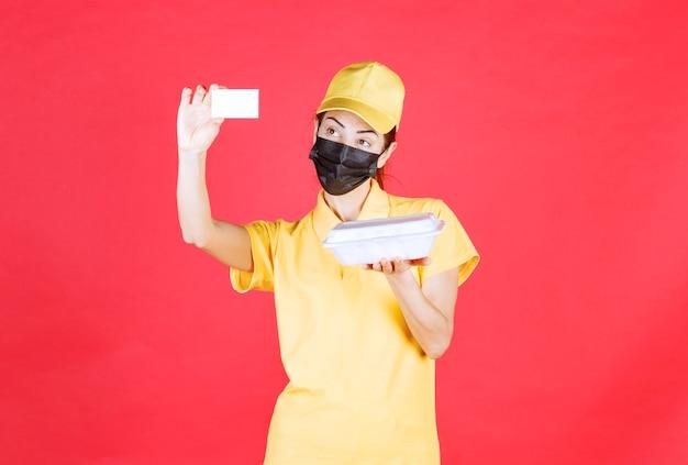 Kurierin in gelber uniform und schwarzer maske, die ein paket zum mitnehmen hält und ihre visitenkarte vorlegt