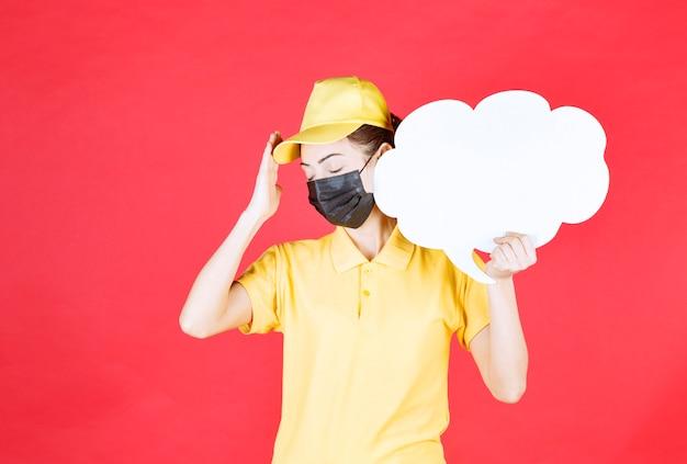 Kurierin in gelber uniform und schwarzer maske, die eine infotafel in wolkenform hält und müde und schläfrig aussieht