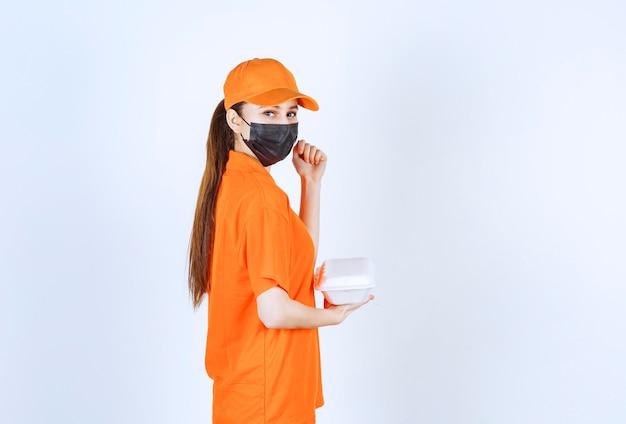Kurierin in gelber uniform und schwarzer maske, die eine plastikbox zum mitnehmen hält und ihre faust zeigt