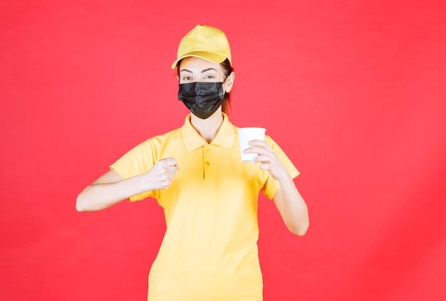 Kurierin in gelber uniform und schwarzer maske, die eine tasse zum mitnehmen hält und ihre faust zeigt