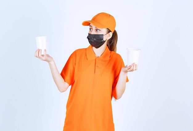 Kurierin in gelber uniform und schwarzer maske, die getränke zum mitnehmen in plastikbechern in beiden händen hält
