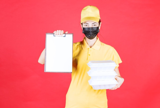 Kurierin in gelber uniform und schwarzer maske, die mehrere pakete zum mitnehmen hält und die unterschriftenliste vorlegt