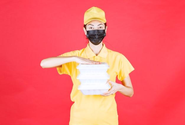 Kurierin in gelber uniform und schwarzer maske, die mehrere pakete zum mitnehmen hält