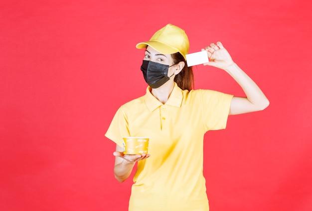 Kurierin in gelber uniform und schwarzer maske liefert einen nudelbecher und präsentiert ihre visitenkarte
