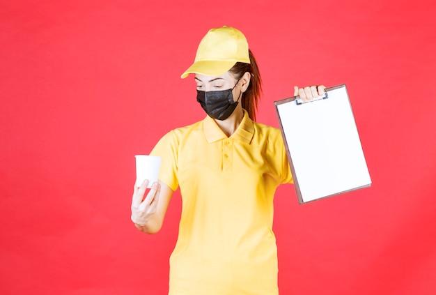 Kurierin in gelber uniform und schwarzer maske mit einer tasse zum mitnehmen und einer kundenliste
