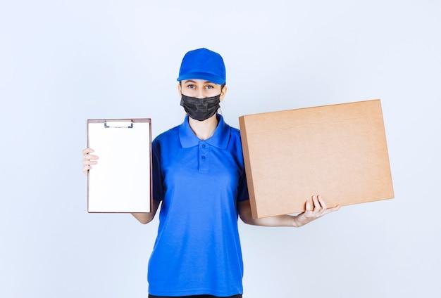 Kurierin in maske und blauer uniform, die ein großes papppaket hält und die checkliste zur unterschrift vorlegt