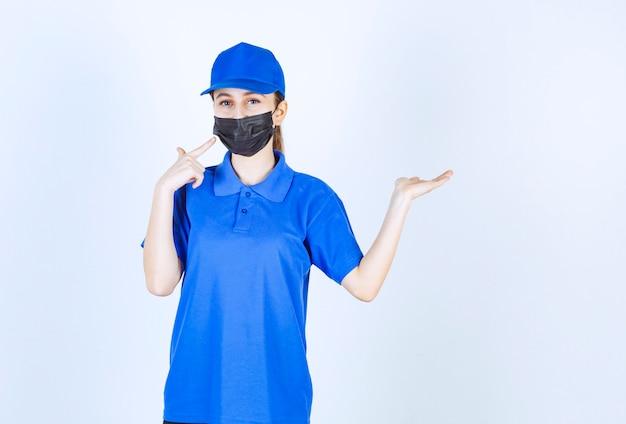 Kurierin in maske und blauer uniform und etwas auf der rechten seite zeigend