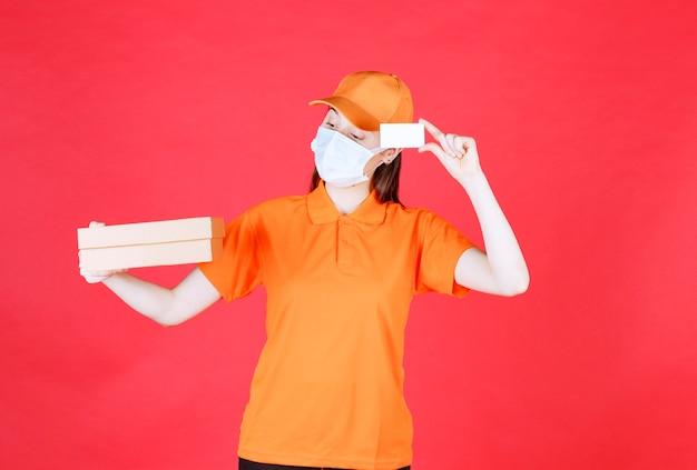 Kurierin in orangefarbenem dresscode und maske, die einen karton hält und ihre visitenkarte vorlegt